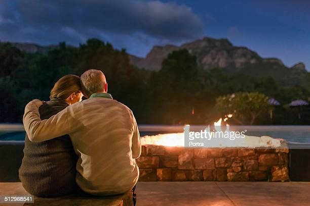 Couple sitting in front of fire pit at night