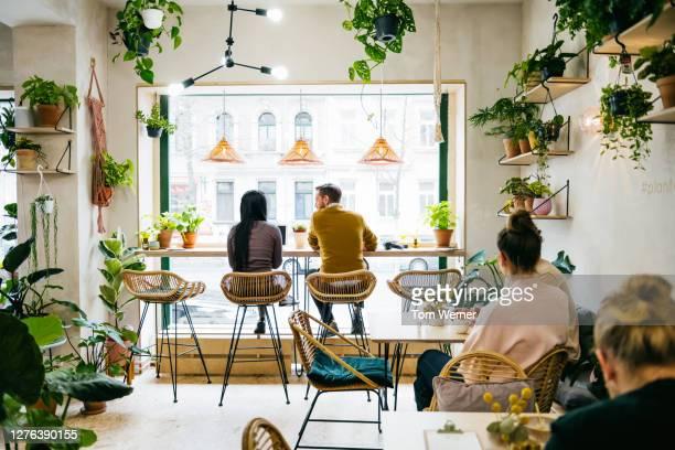 couple sitting in front of window in quirky café - vida en la ciudad fotografías e imágenes de stock