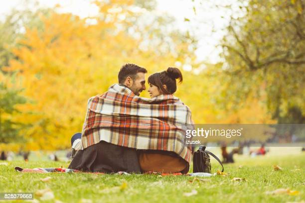 couple sitting in garden on a autumn day - hyde park london stock photos and pictures