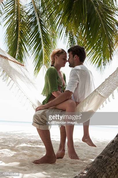 couple sitting in hammock on beach - legs apart stock photos and pictures