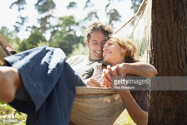 couple sitting in hammock - koppel stockfoto's en -beelden