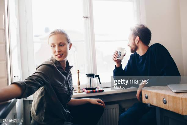 Couple sitting in kitchen drinking coffee by window at home