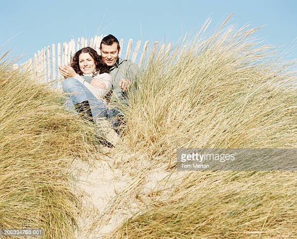 Couple sitting in long grass on sand dune, smiling, low angle view