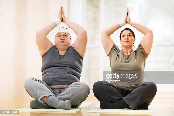 couple sitting in lotus position and exercising yoga. - fat woman sitting on man stock pictures, royalty-free photos & images
