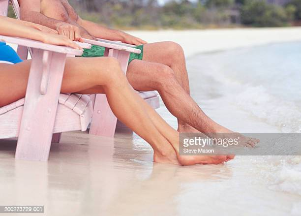 Couple sitting in lounge chairs on beach, low section