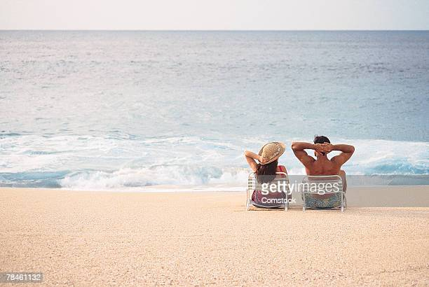 Couple sitting in lounge chairs on beach