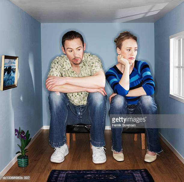 couple sitting in mall living room, looking depressed - heterosexuelles paar stock-fotos und bilder