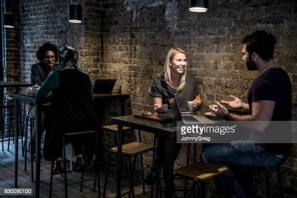 Couple sitting in modern cafe smiling and talking with laptop on table