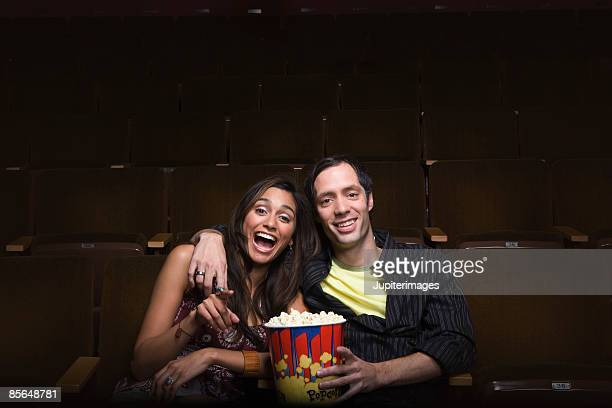 Couple sitting in movie theatre laughing