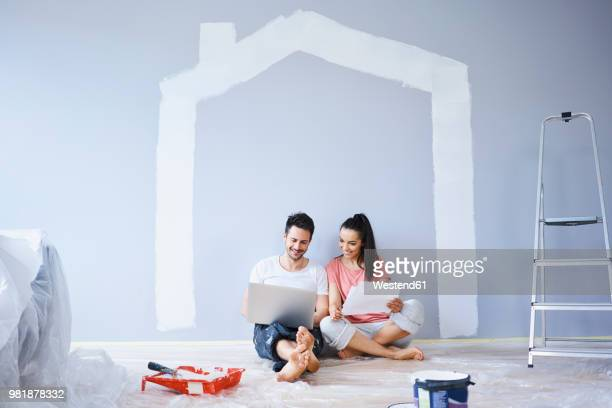 couple sitting in new apartment using laptop - reform stock pictures, royalty-free photos & images