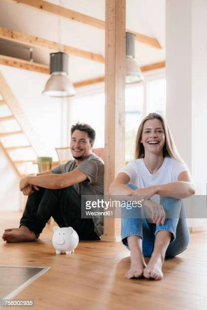 Couple sitting in new home with a piggy bank