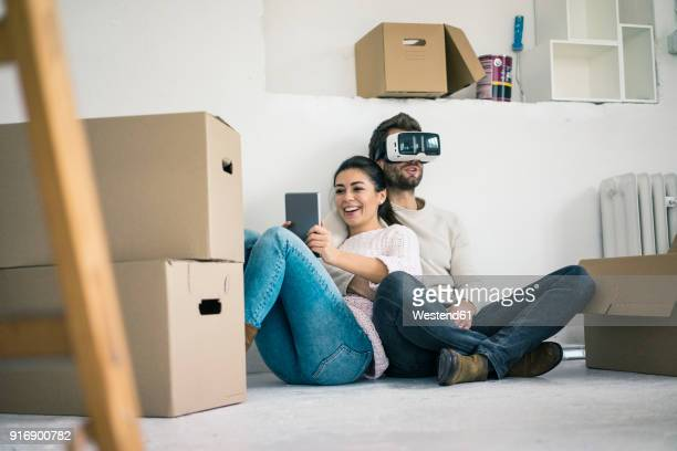 couple sitting in new home with man wearing vr glasses - surrounding stock pictures, royalty-free photos & images