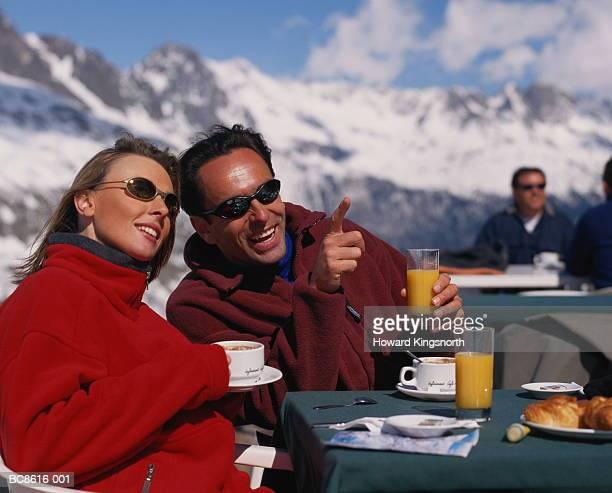 couple sitting in outdoor cafe, mountains in distance, france - fleecejas stockfoto's en -beelden