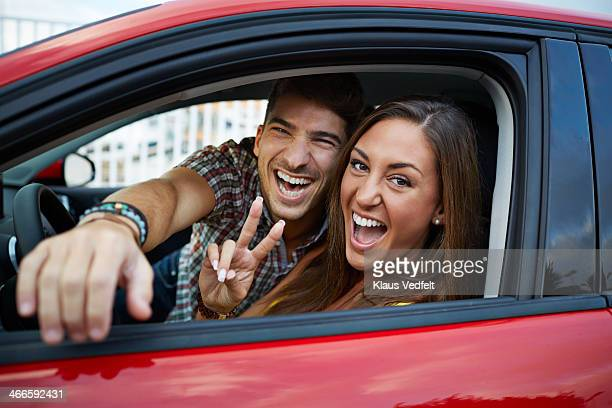 Couple sitting in red car and laughing