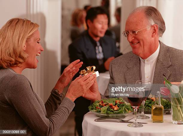 couple sitting in restaurant, man giving woman gift - sugar daddy stock photos and pictures
