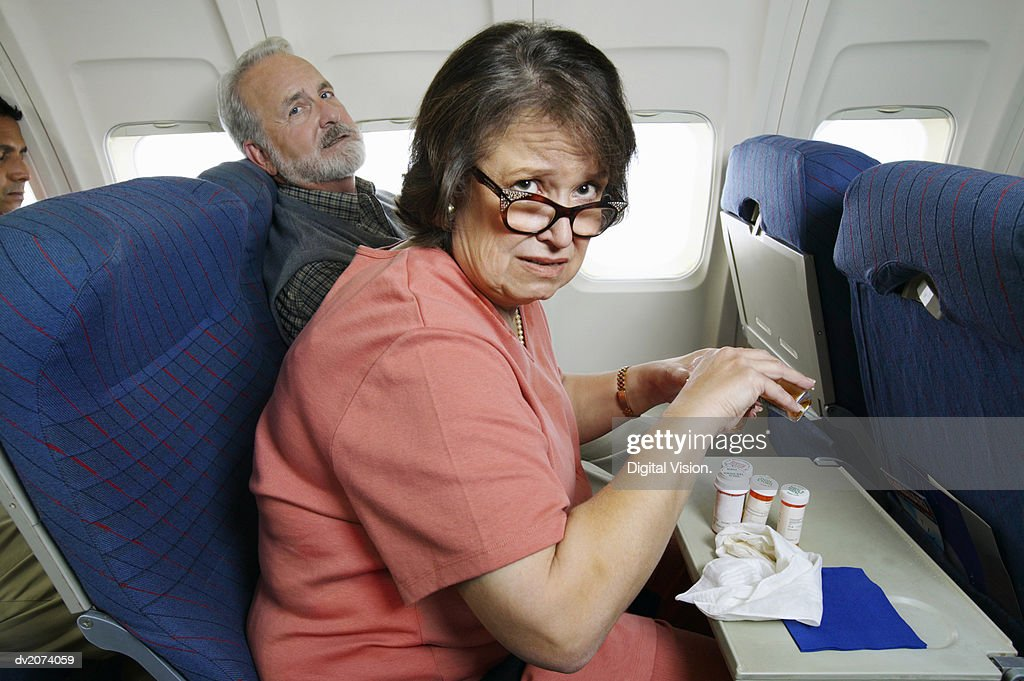 Couple Sitting in Seats in an Aeroplane Cabin, Woman With Pills : Stock Photo