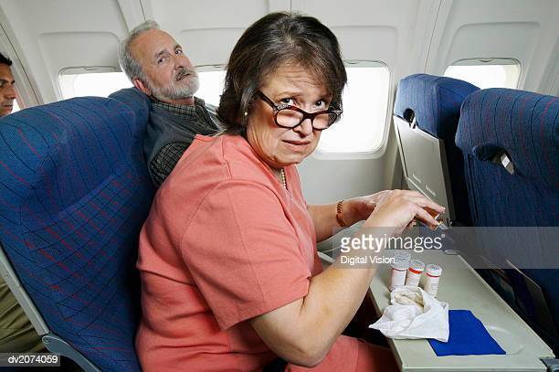 couple sitting in seats in an aeroplane cabin, woman with pills - passagier stock-fotos und bilder