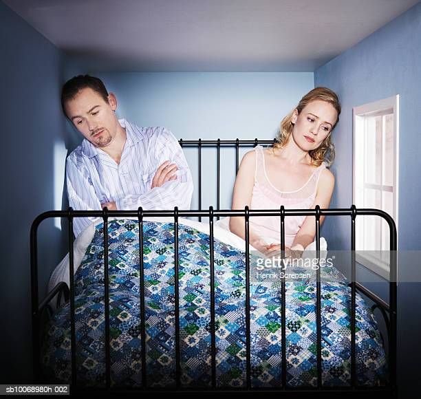 couple sitting in small bed room, looking depressed - women in slips stock pictures, royalty-free photos & images