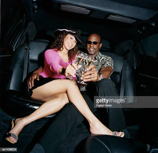 couple sitting in the back seat of limousine drinking champagne - short skirts in cars stock photos and pictures