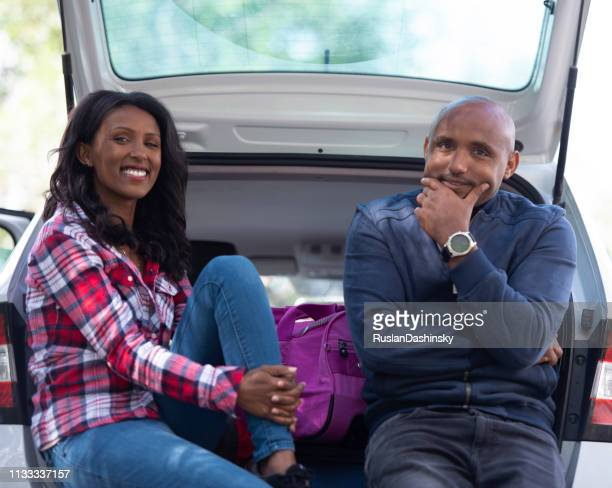 Couple sitting in the car trunk.