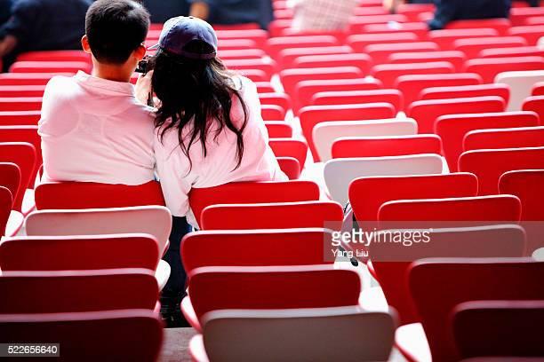 a couple sitting in the national stadium - stadio olimpico nazionale foto e immagini stock