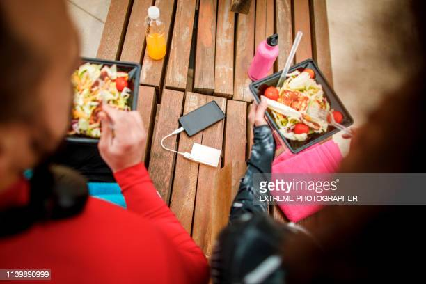 couple sitting in the park, eating a healthy protein salad from a plastic casing, with a mobile phone charging on a power bank between them - plastic plate stock photos and pictures