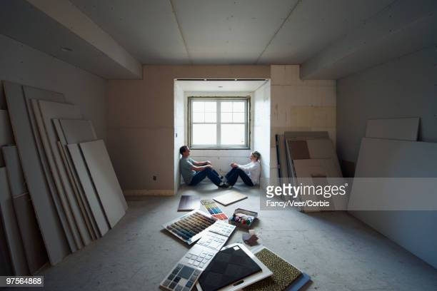 Couple sitting in unfinished home