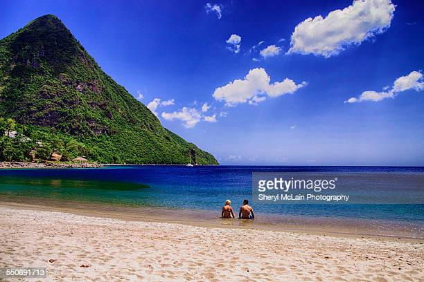 couple sitting in water on white, sandy beach - st. lucia stock pictures, royalty-free photos & images