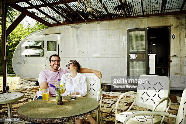 Couple sitting in yard in front of retro trailer