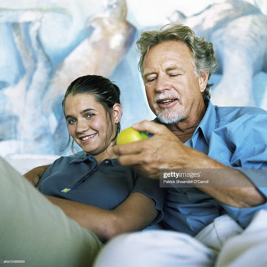 Couple sitting, man holding fruit : Stockfoto