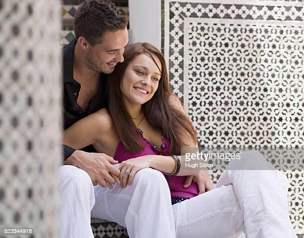 couple sitting near mosaic moroccan wall - hugh sitton stockfoto's en -beelden