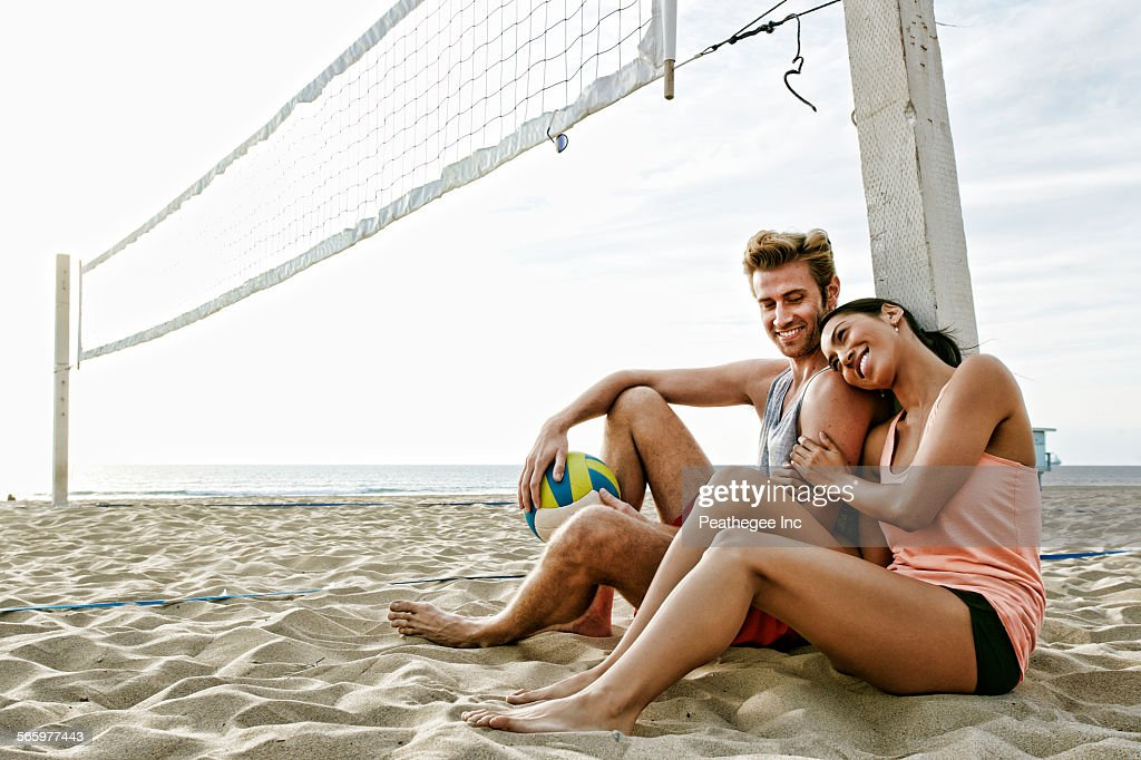 Couple sitting near volleyball net on beach : Stock-Foto