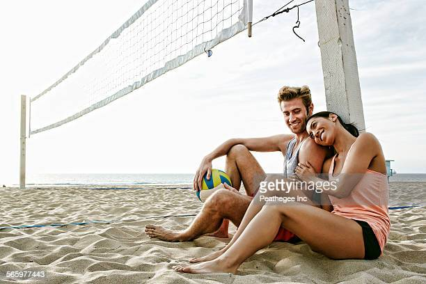 couple sitting near volleyball net on beach - beachvolleybal stockfoto's en -beelden