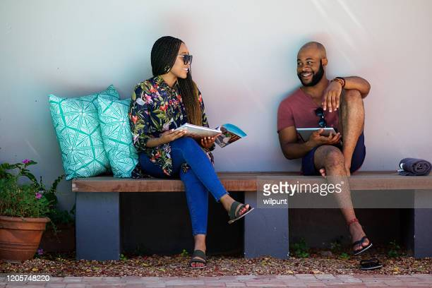 couple sitting next to the pool relaxing on a bench reading and smiling - nature magazine stock pictures, royalty-free photos & images