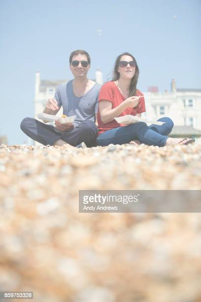 Couple sitting on a beach eating fish and chips