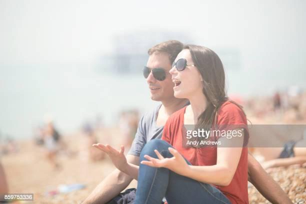 Couple sitting on a beach talking