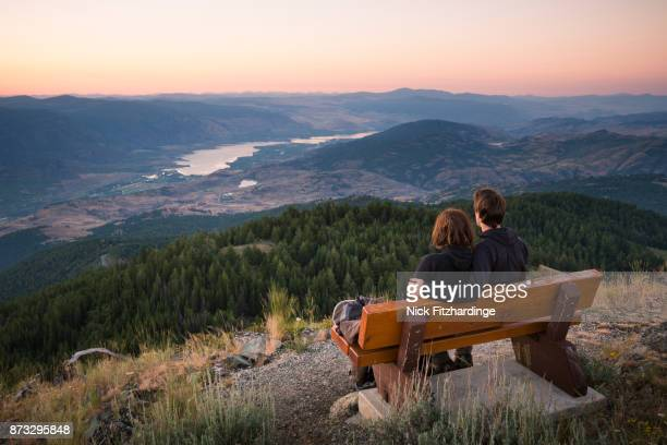 couple sitting on a bench looking at osoyoos and the south okanagan from the summit of mt kobau, british columbia, canada - okanagan valley stock pictures, royalty-free photos & images