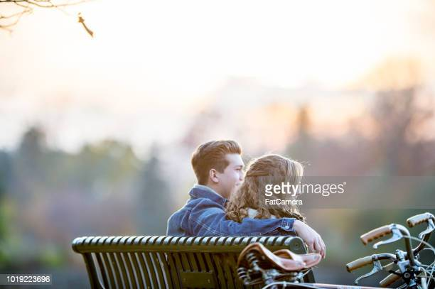 couple sitting on a bench - fatcamera stock pictures, royalty-free photos & images