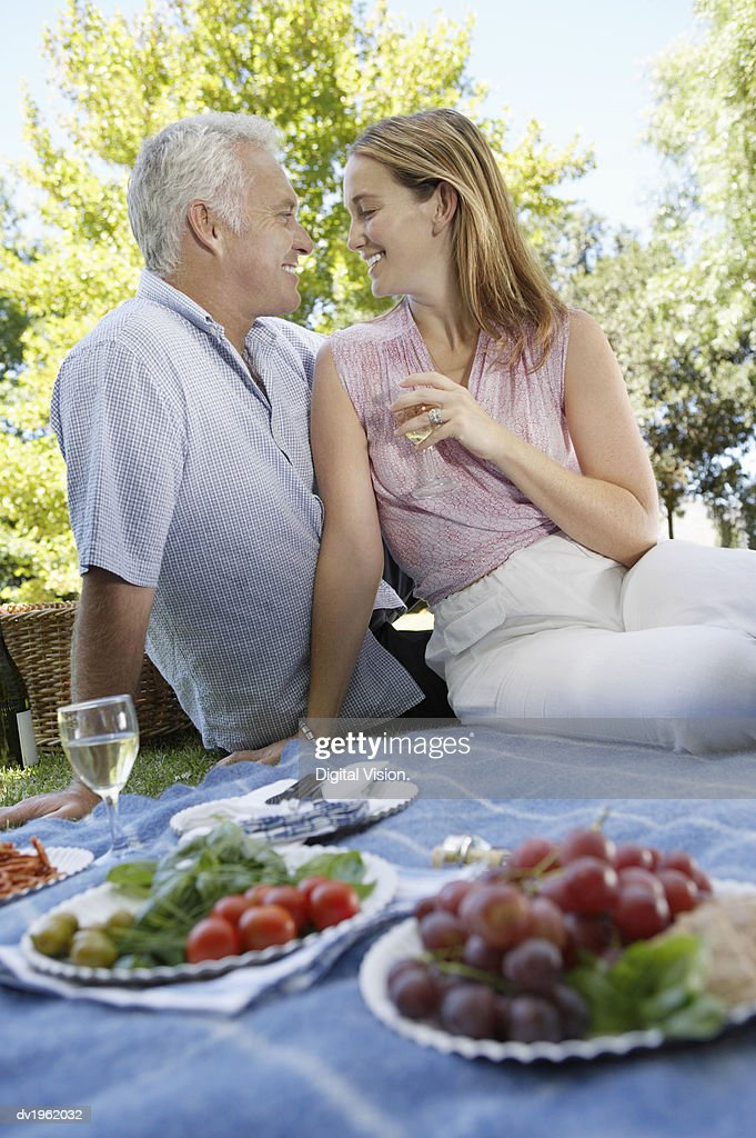 Couple Sitting on a Blanket Having a Picnic : Stock Photo