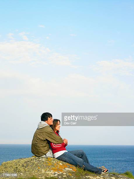 Couple sitting on a cliff looking out to sea.