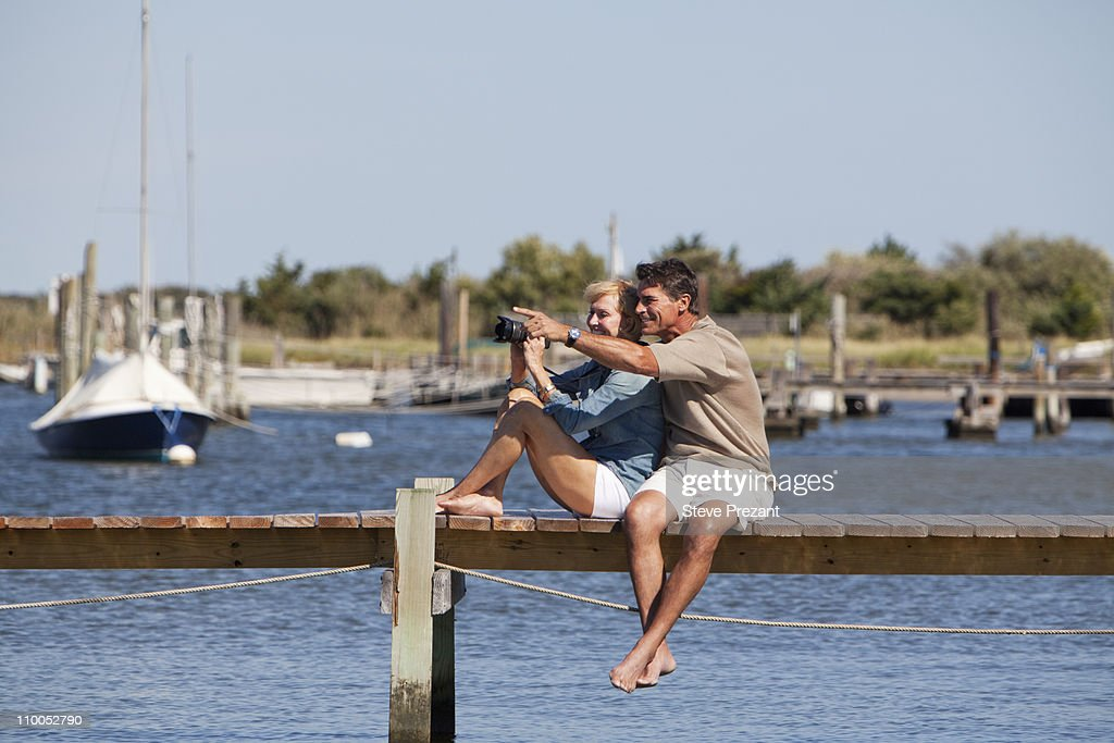 Couple sitting on a dock : Stock Photo