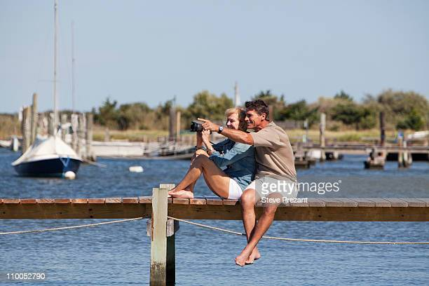 couple sitting on a dock - pointing at camera stock photos and pictures