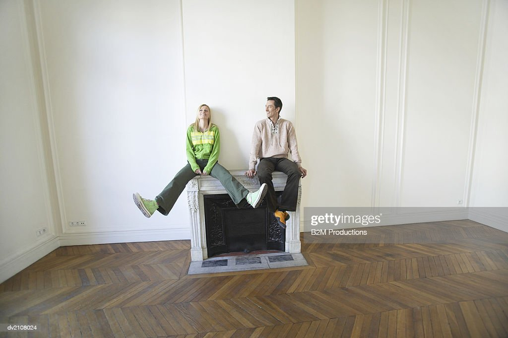 Couple Sitting on a Fireplace in an Empty New House : Stock Photo