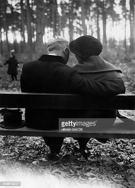 A couple sitting on a park bench the man has his arm around the woman 1933 Photographer PresseIllustrationen Heinrich Hoffmann Vintage property of...