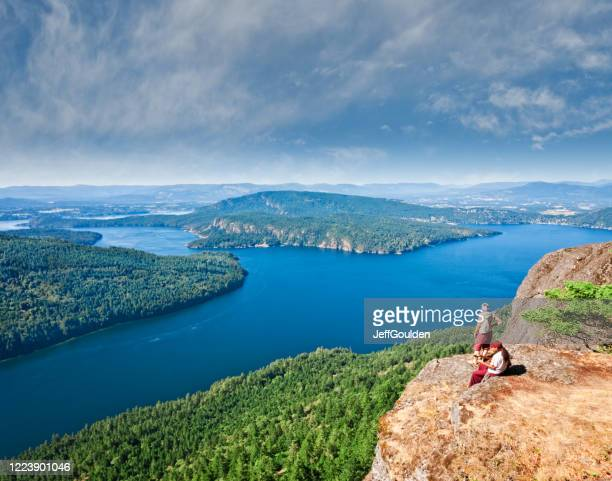 couple sitting on a rock ledge - jeff goulden stock pictures, royalty-free photos & images