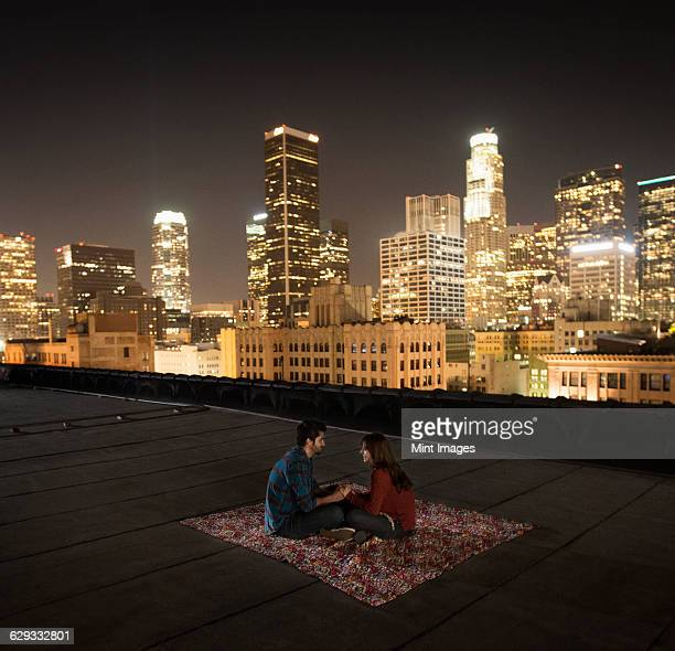 A couple sitting on a rug on a rooftop overlooking a city lit up at night.