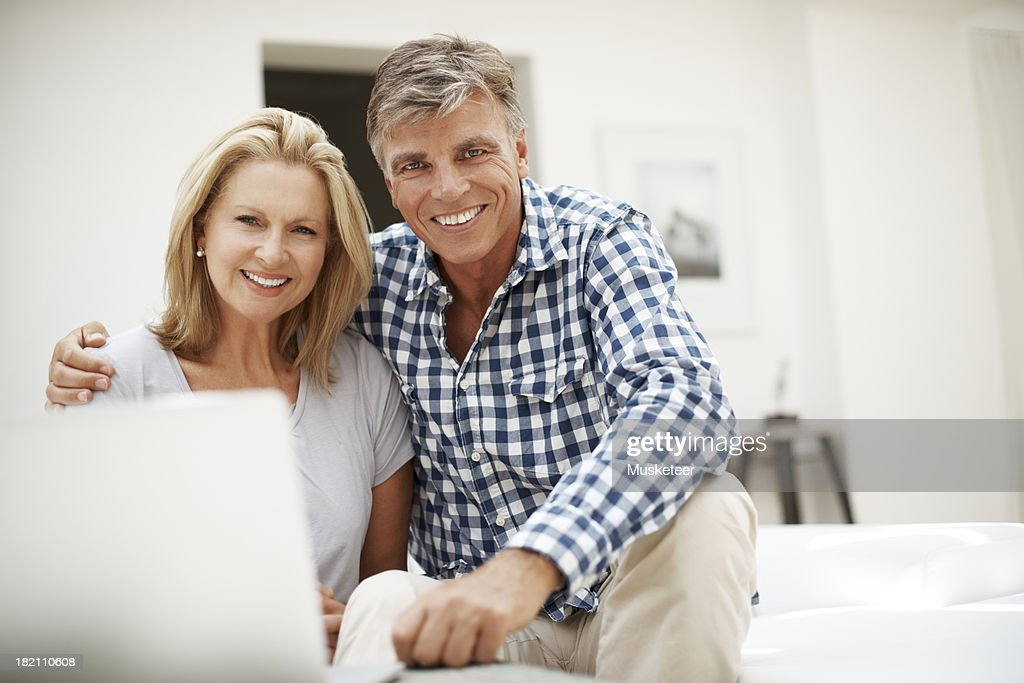 Couple sitting on a sofa looking into camera : Stock Photo