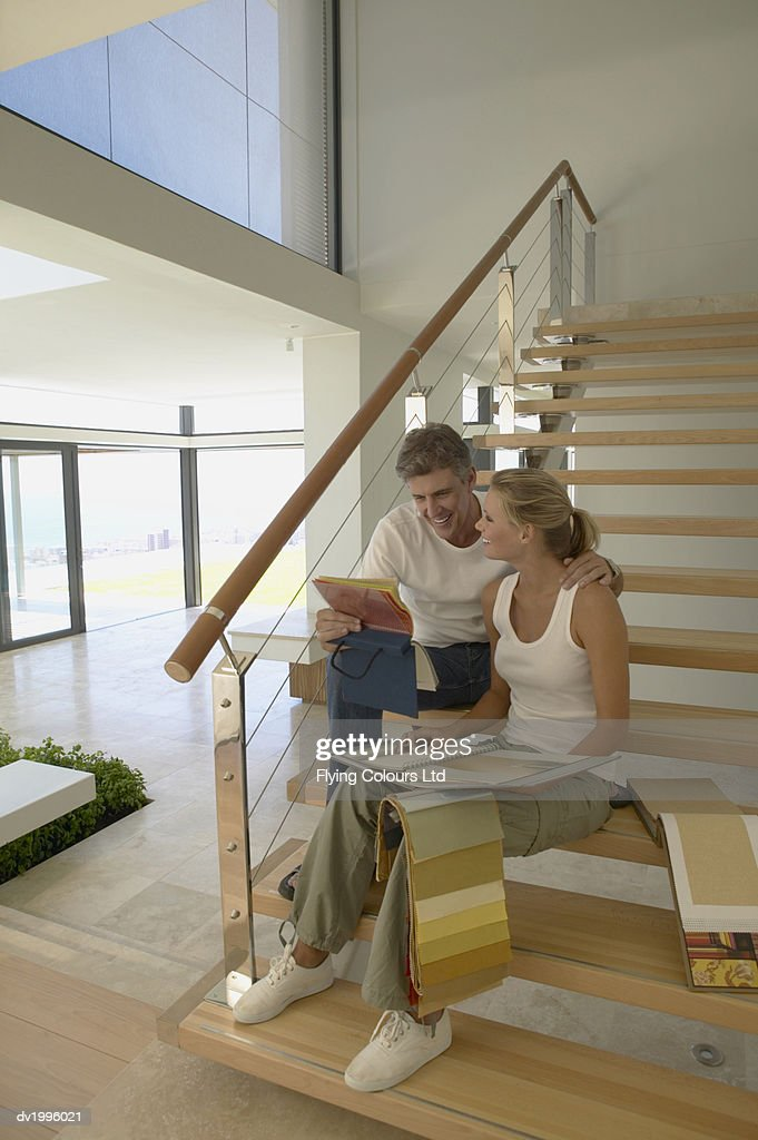 Couple Sitting on a Staircase in an Apartment Looking at Color Swatches : Stock Photo