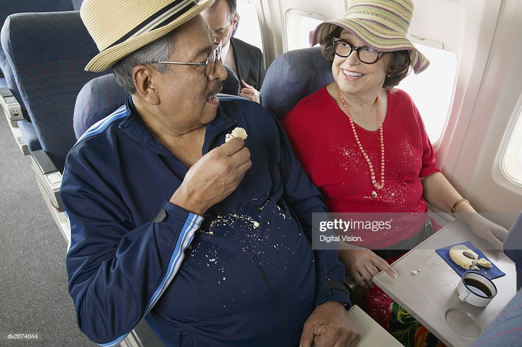 Couple Sitting on an Aeroplane With Crumbs Over Their Clothing From Biscuits : Stock Photo