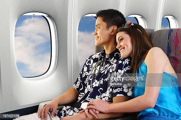 Couple sitting on an airplane headed towards honeymoon
